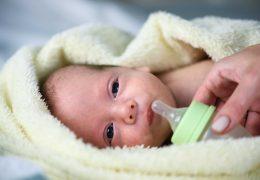 newborn-baby-boy-with-plastik-bottle-closeup